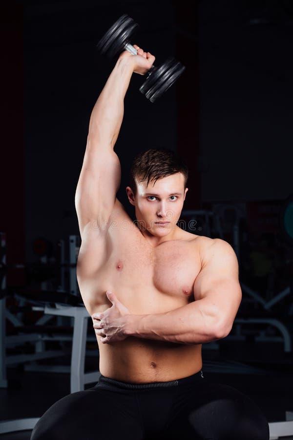 Séance d'entraînement professionnelle de bodybuilder avec le barbell se reposant sur le banc au gymnase Grande formation musculai image libre de droits