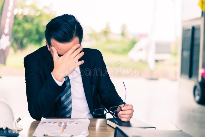 Séance d'homme d'affaires et sa tête étreinte par main, il est se sentir de soumis à une contrainte et tristesse, photo libre de droits