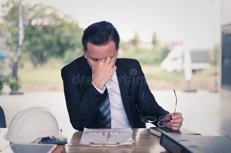 séance d'homme d'affaires et sa tête étreinte par main, il est se sentir de soumis à une contrainte et tristesse de faillite comm photo stock