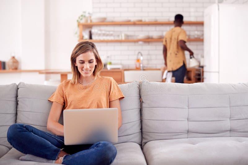 Séance de détente de femme sur l'ordinateur de Sofa At Home Using Laptop avec l'homme dans la cuisine derrière images stock