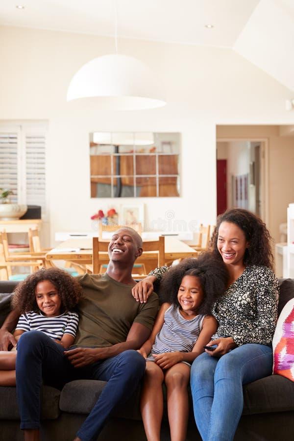 Séance de famille sur le film de Sofa At Home And Watching à la TV ensemble photos stock