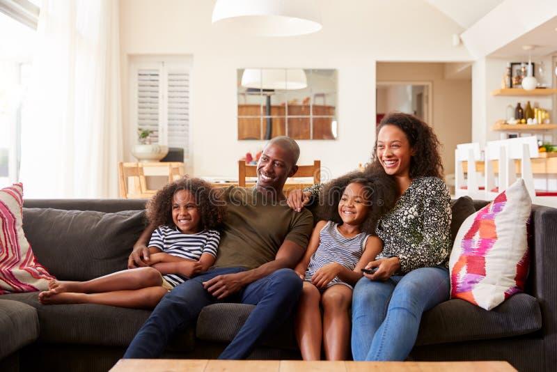 Séance de famille sur le film de Sofa At Home And Watching à la TV ensemble photo stock