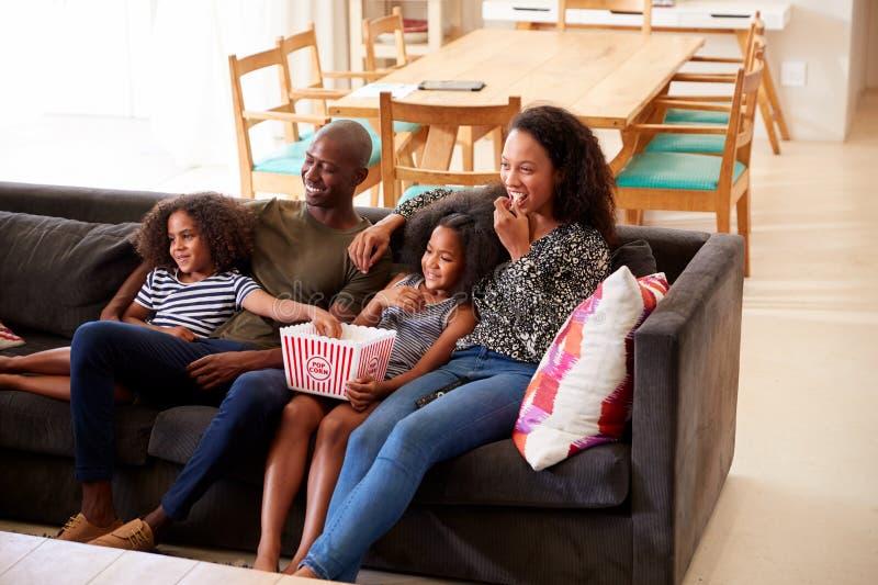 Séance de famille sur Sofa At Home Eating Popcorn et le film de observation ensemble photographie stock