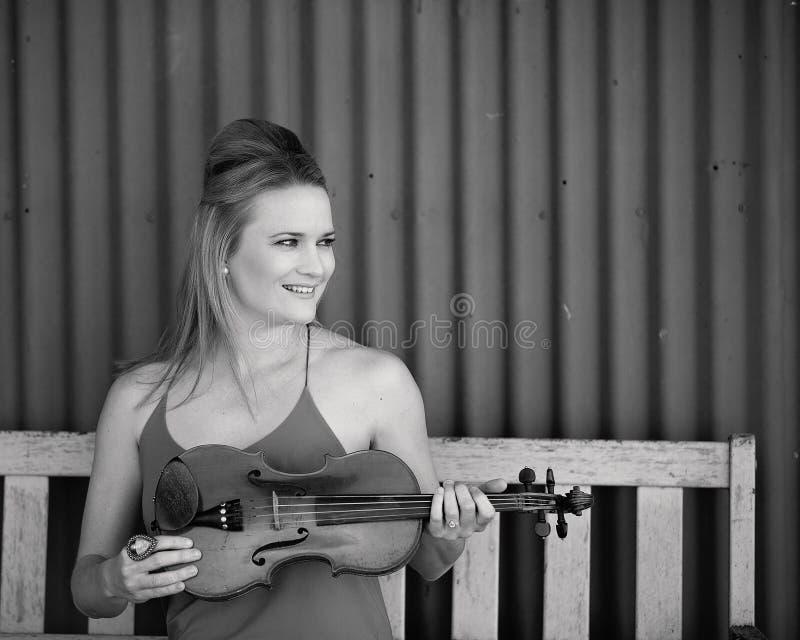 Séance de femme avec le violon 1893 antique dans monotone photos libres de droits