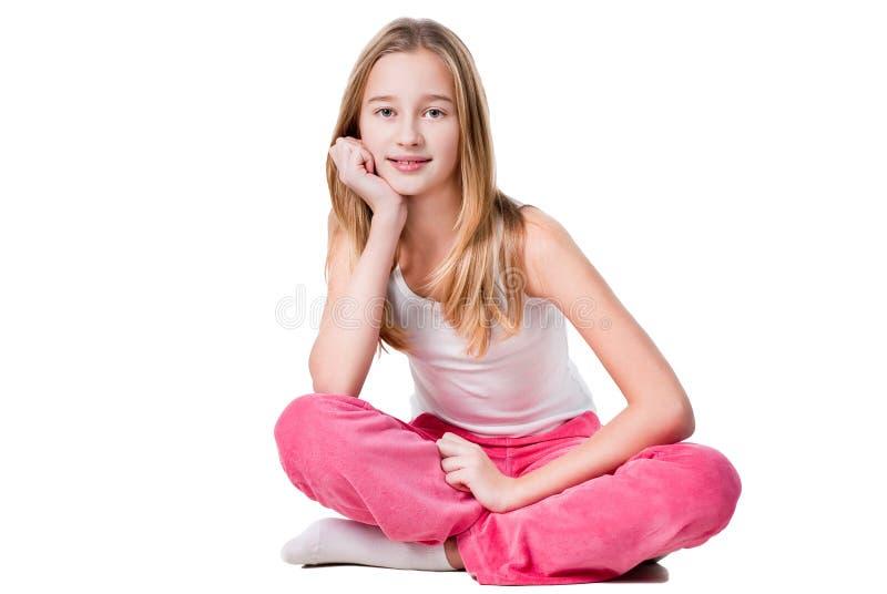 Séance de l'adolescence de fille d'isolement sur le blanc photographie stock