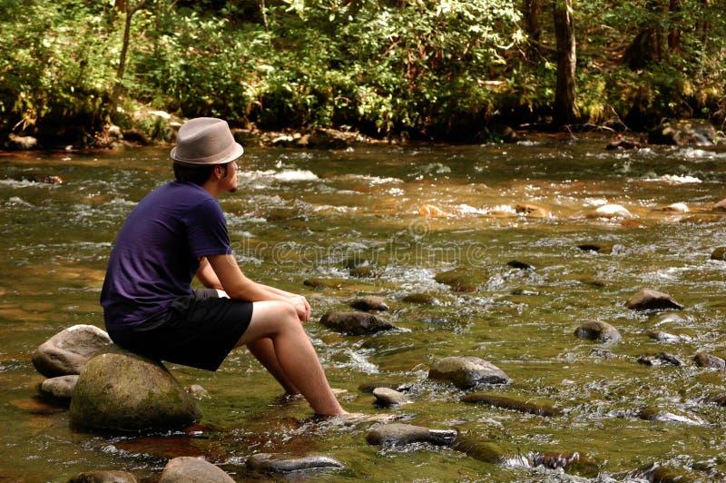 Séance de l'adolescence sur des roches de fleuve photographie stock