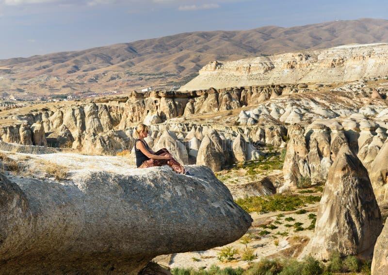 Séance de touristes de femme sur la falaise Vue des maisons de caverne dans Cavusin Cappadocia La Turquie photographie stock