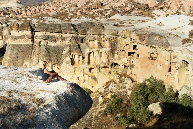 Séance de touristes de femme sur la falaise Vue des maisons de caverne dans Cavusin Cappadocia La Turquie photos libres de droits