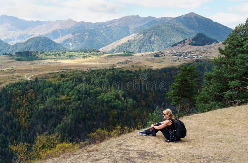 Séance de touristes de femme sur la montagne Vue sur le village de montagnes et d'Omalo georgia photo libre de droits