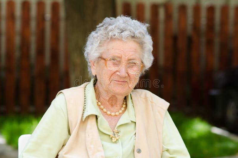 Séance et détente heureuses de dame âgée images stock