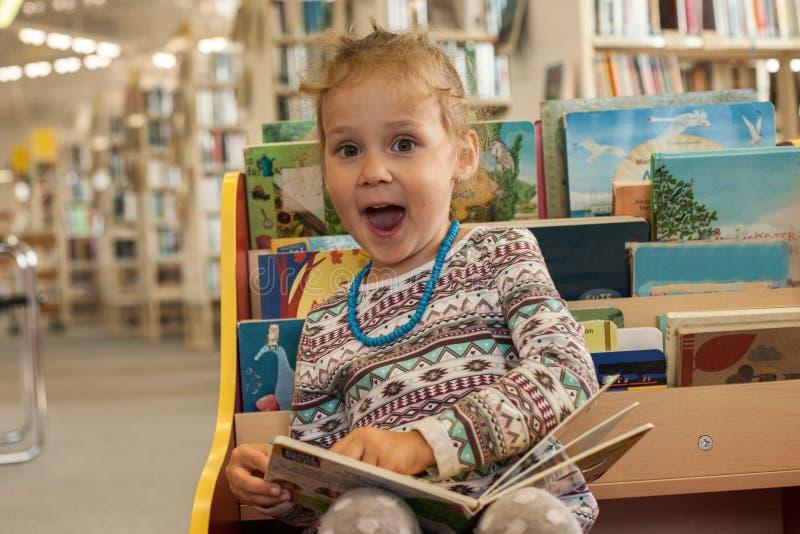 Séance et lecture de petite fille d'élève du cours préparatoire un livre dans la bibliothèque Enfant avec des livres près d'une b images stock