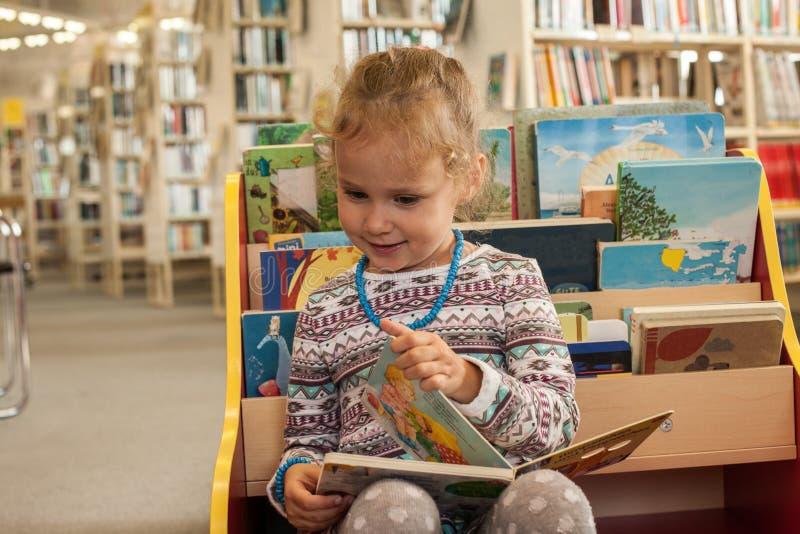 Séance et lecture de petite fille d'élève du cours préparatoire un livre dans la bibliothèque Enfant avec des livres près d'une b image stock