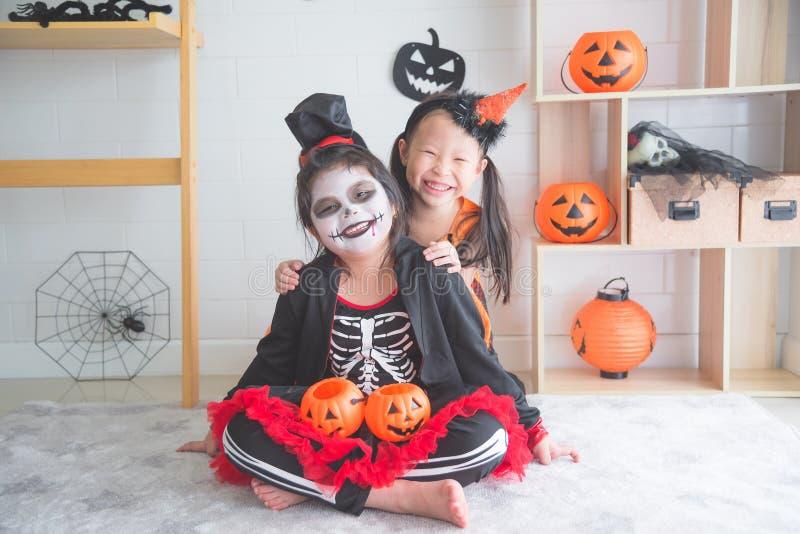 Séance et sourire de filles dans la chambre décorée pour le jour de Halloween photo libre de droits