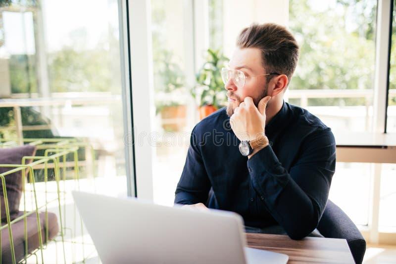 Séance exécutive amicale devant l'ordinateur portable dans son bureau Grande fenêtre au fond Regardant loin, rêvassant photo libre de droits