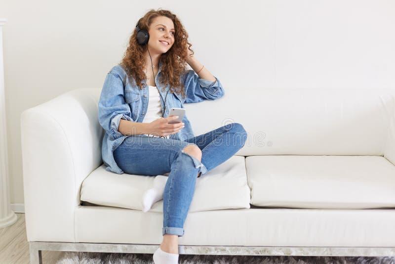 Séance femelle agréable gaie sur le sofa, regardant de côté, tenant son smartphone, ayant des écouteurs, écoutant la musique préf photos libres de droits