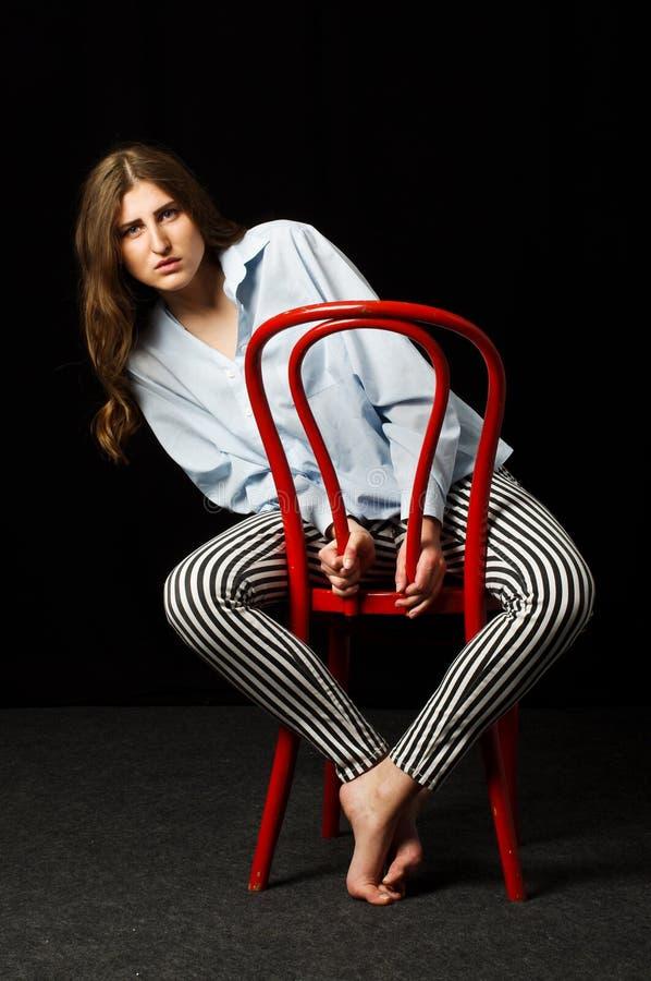 Séance femelle apathique sur la chaise rouge dans le studio foncé photographie stock