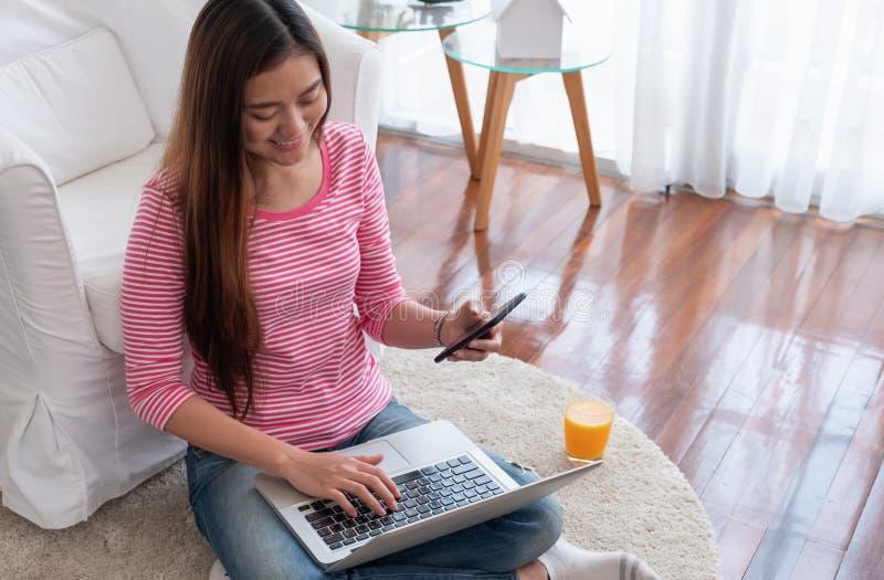 Séance femelle asiatique sur le mobile d'utilisation de plancher avec des achats d'ordinateur portable dessus photos libres de droits