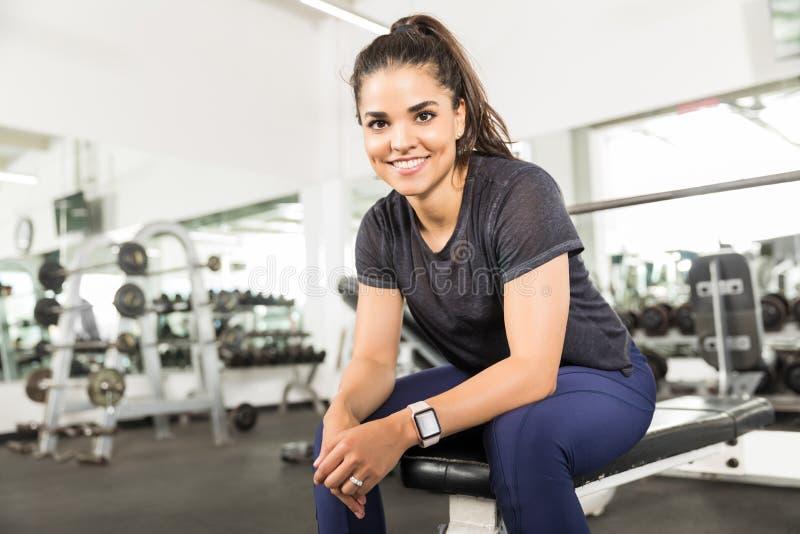 Séance femelle saine de sourire sur le banc au centre de fitness photographie stock libre de droits