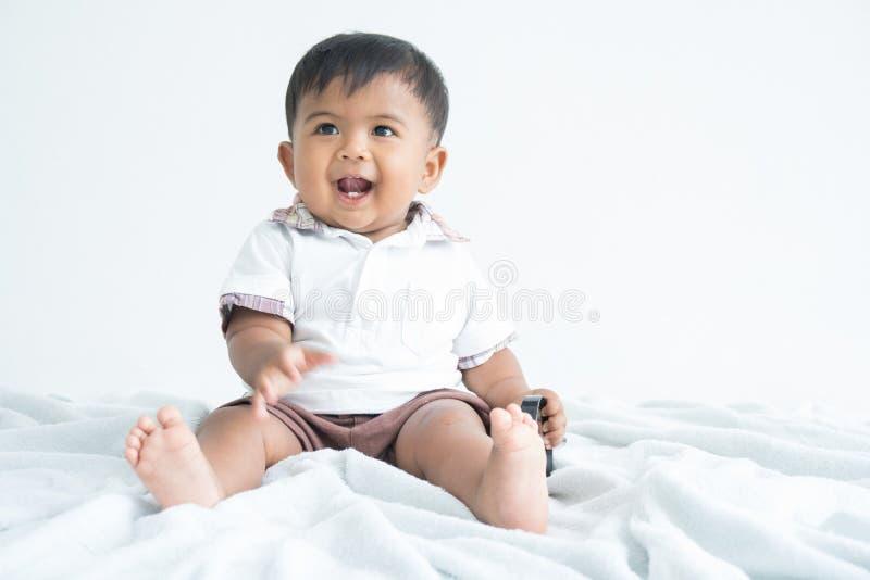 Séance mignonne et sourire de petit garçon photographie stock libre de droits
