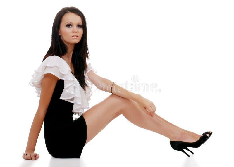 Séance noire blanche s'usante de robe de femme de Brunette photos stock