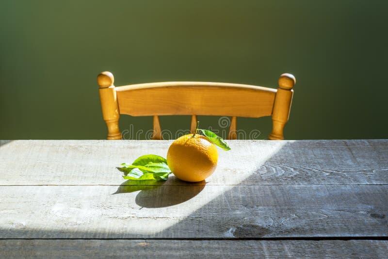 Séance orange sélectionnée fraîche de déchirure devant la chaise au bois t de ferme images libres de droits