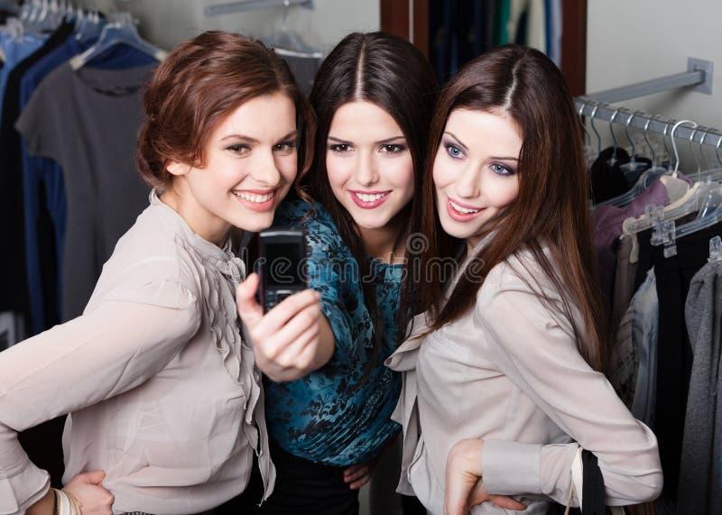 Séance photo de filles au téléphone portable après l'achat photographie stock libre de droits