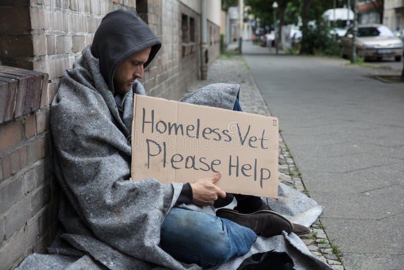 Séance sans abri masculine sur une rue demandant l'aide photos libres de droits