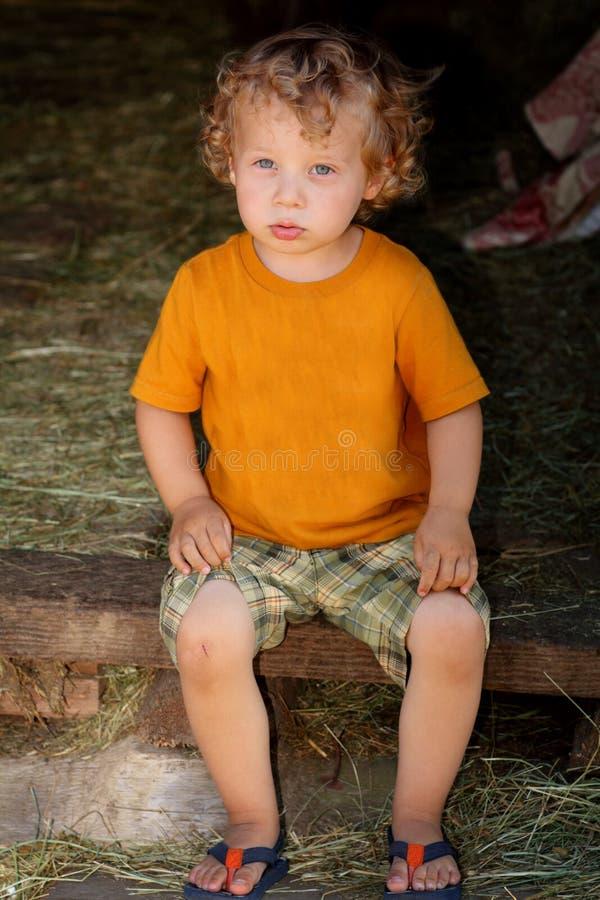 Séance sombre d'enfant en bas âge image stock