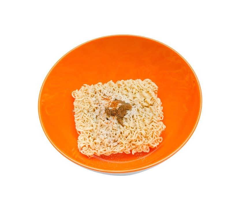 Séchez la nouille instantanée dans la cuvette orange sur le fond blanc photos stock