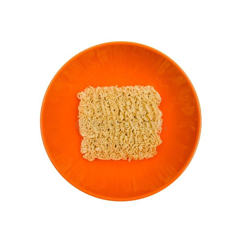 Séchez la nouille instantanée dans la cuvette orange sur le fond blanc photo stock
