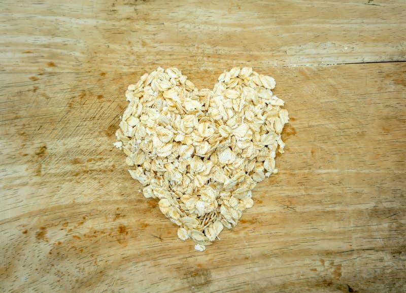 Séchez la pile de flocons d'avoine roulées dans la forme de coeur sur le conseil en bois guérissez photo stock