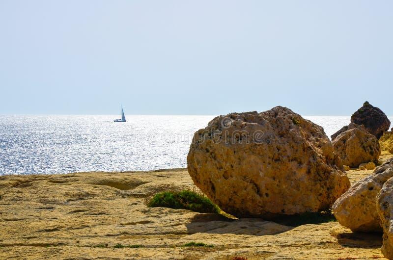 Séchez la plage rocheuse et un voilier sur la mer Méditerranée images stock