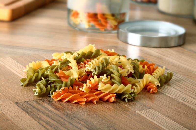 Séchez les pâtes tricolores de rotini sur le bureau en bois de cuisine photos libres de droits