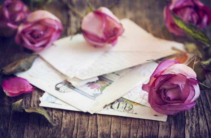 Séchez les roses roses et la vieille lettre sur le fond en bois photo stock