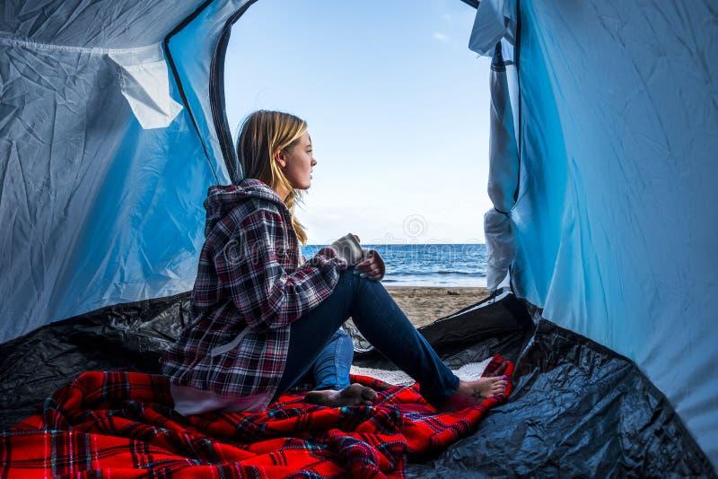 Séjour agréable blond de jeune femme sur la tente à l'alternative campante de liberté aucun rulez sur et devant la mer l'ind?pend image libre de droits