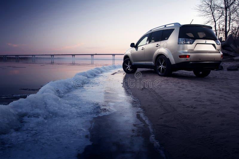 Séjour d'Outlander de Mitsubishi de voiture sur la côte de glace au coucher du soleil d'hiver images libres de droits