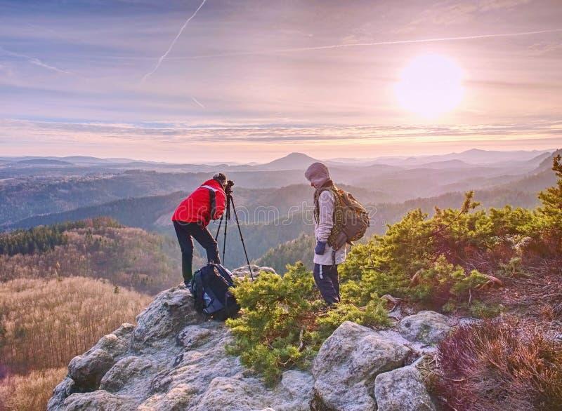 Séjour de deux personnes au trépied sur le fond d'une gamme de montagne photos stock