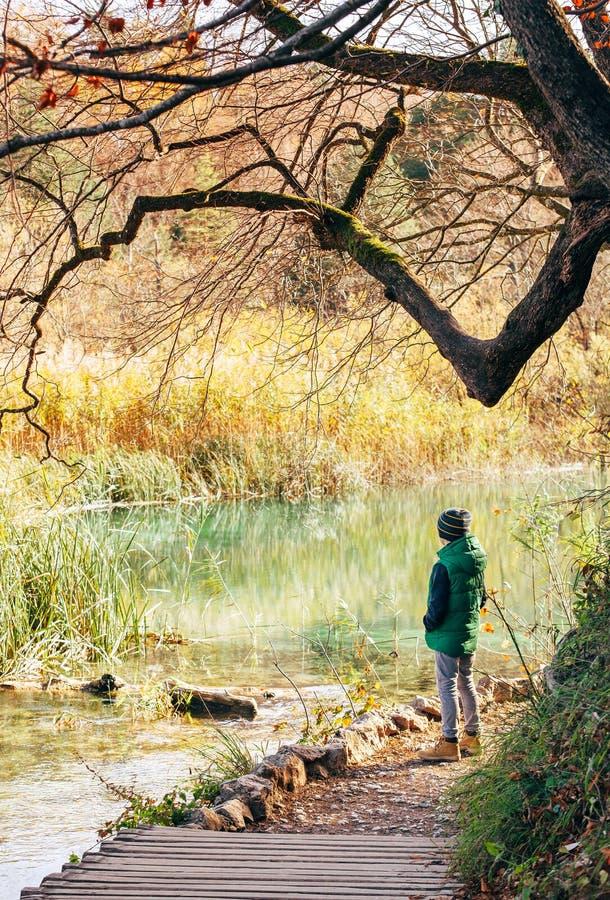 Séjour de garçon près d'étang en parc d'automne, jours ensoleillés d'automne de bout photos stock
