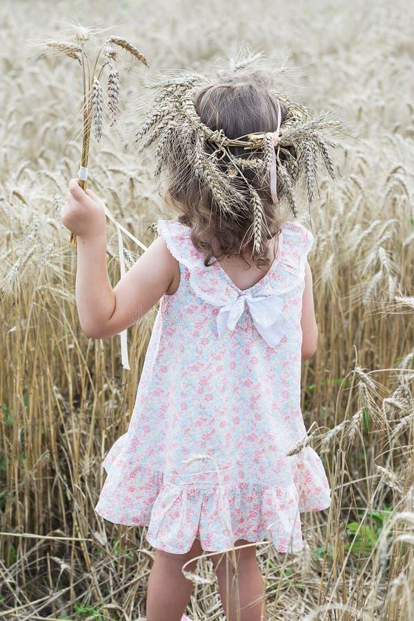 Séjour de petite fille avec la guirlande du blé sur sa tête et tenir un bouquet de blé images libres de droits