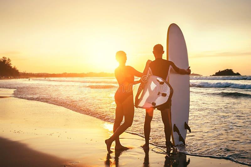 Séjour de surfers de couples sur la plage d'océan de coucher du soleil photos libres de droits