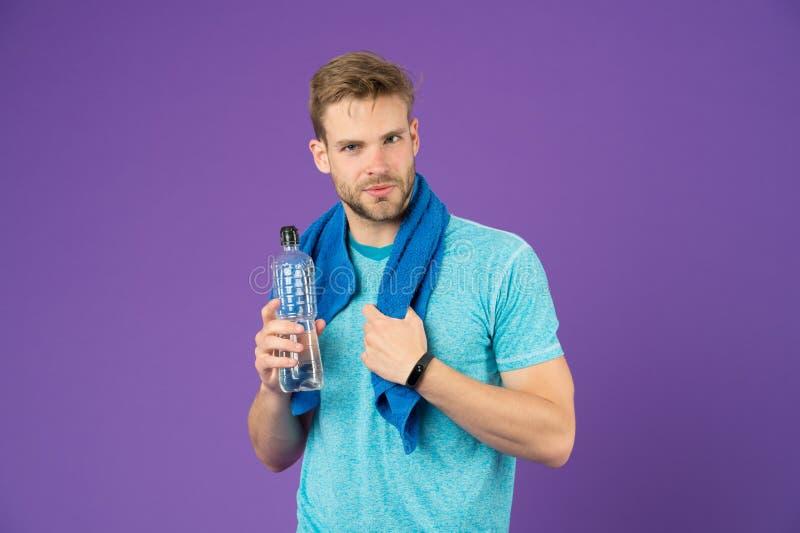 Séjour hydraté Buvez une certaine eau L'athlète d'homme avec la serviette sur des épaules tient la bouteille d'eau Vêtements de s photos stock