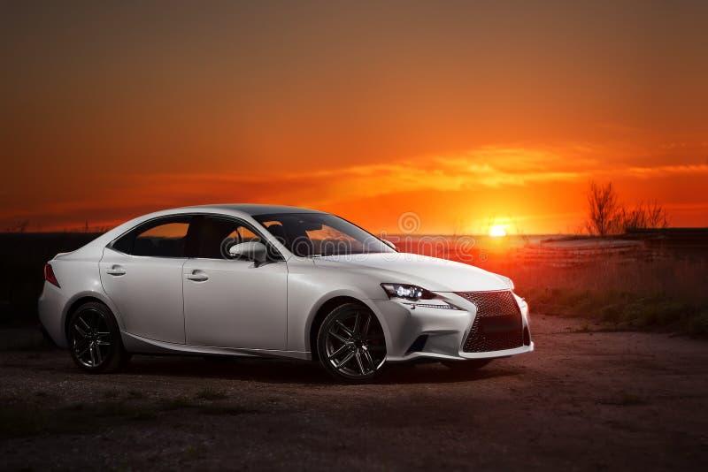 Séjour moderne blanc de voiture sur la route au beau coucher du soleil images stock