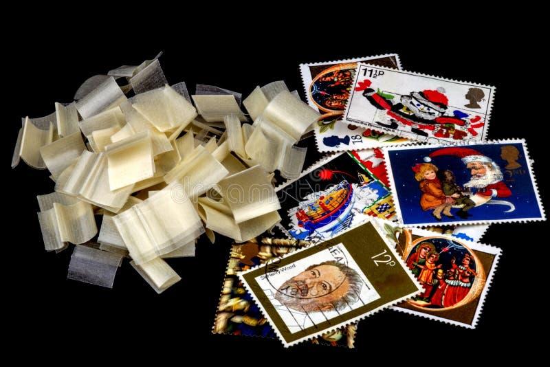 Sélection des timbres et des charnières BRITANNIQUES de timbre sur le noir photos libres de droits