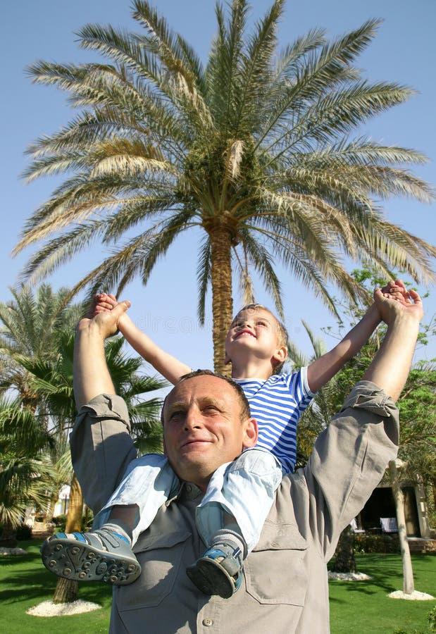 Sénior com a criança em ombros na frente da palma fotografia de stock