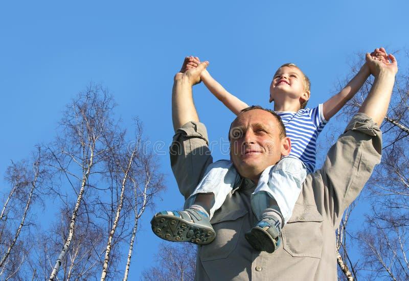 Sénior com a criança em ombros na frente do vidoeiro foto de stock