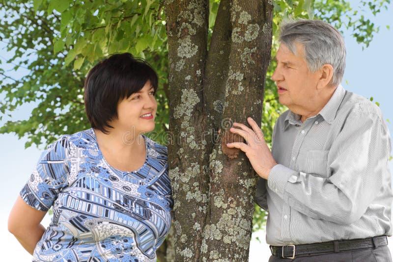 Sénior e sua filha que estão a árvore próxima fotografia de stock