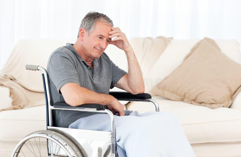 Sénior em sua cadeira de rodas que tem uma dor de cabeça foto de stock royalty free