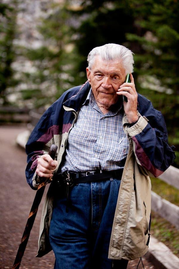 Sénior no telefone de pilha fotografia de stock