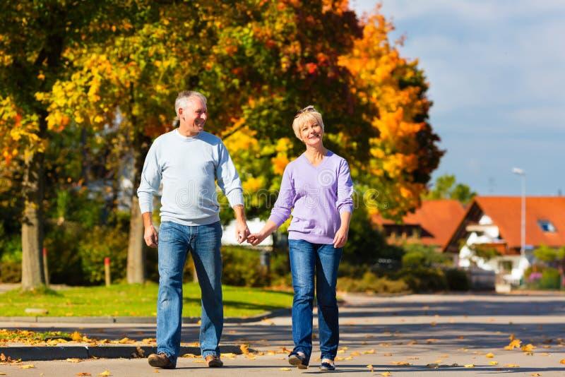 Séniores no outono ou na queda que andam em conjunto fotos de stock