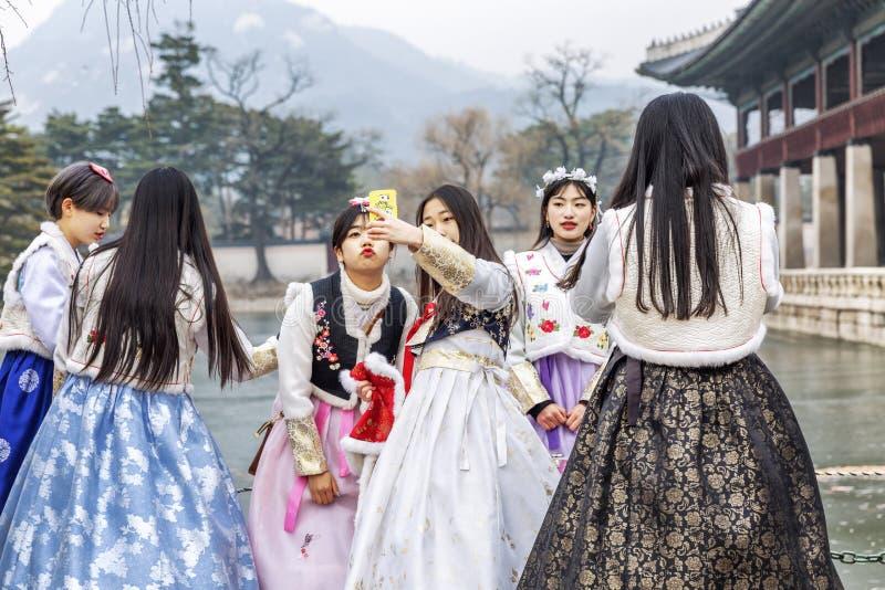 Séoul, Corée du Sud, 12/30/2017 : Les filles coréennes dans les hanboks prennent un selfie en parc d'hiver Plan rapproch? photos stock